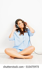 Gorgeous happy young brunette woman in blue male oversize shirt, listening to music on headphones, smiling. Studio lighting, retouched.