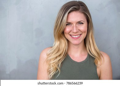 Gorgeous headshot of young bright cheerful sincere smiling caucasian blond female against a gray background