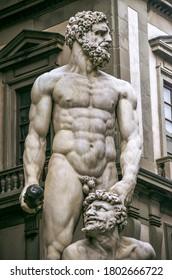 Magnífica escultura de Hércules con un edificio detrás