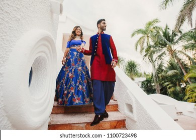 Gorgeous Hindu groom in blue and red sherwani and bride in blue lehenga pose on the stairs in white house with greenery