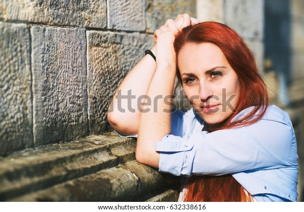 Gorgeous hipster redhead girl leaning against a stone wall and enjoying the first spring sunbeams. Harmony between nature and human. Peaceful and calm emotions.