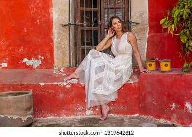 A gorgeous Hispanic Brunette model poses outdoors in home environment