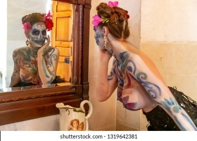 A gorgeous Hispanic Brunette model poses with traditional skull sugar makeup paint for a Mexican festival.