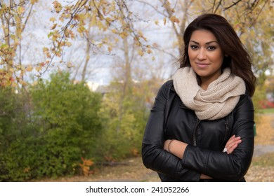 Gorgeous Hispanic woman posing with arms cross outside during autumn