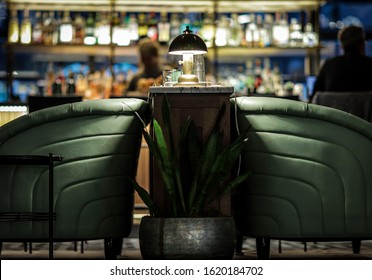 Gorgeous interior of a mid century modern speakeasy bar with green leather couches