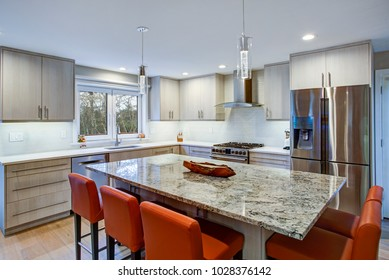 Gorgeous kitchen design features ivory cabinets flanking modern steel hood, linear marble tile backsplash, island with granite counter top and red leather bar stools.
