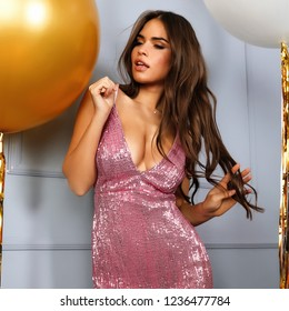 Gorgeous lady in bright sparkling pink dress with decollete standing with two balloons white and golden color. Beautiful makeup and hairstyle. Hand in the long brown hair. Indoor fashion shooting.