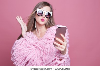 Gorgeous lady dressed in funky bushy coat, wears make up, makes video call via smart phone and headphones, looking at gadget screen, taking selfie sending kiss to boyfriend, standing over pink wall.