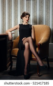 Gorgeous lady in elegant evening black dress with deep cut in stockings. Girl posing near table.