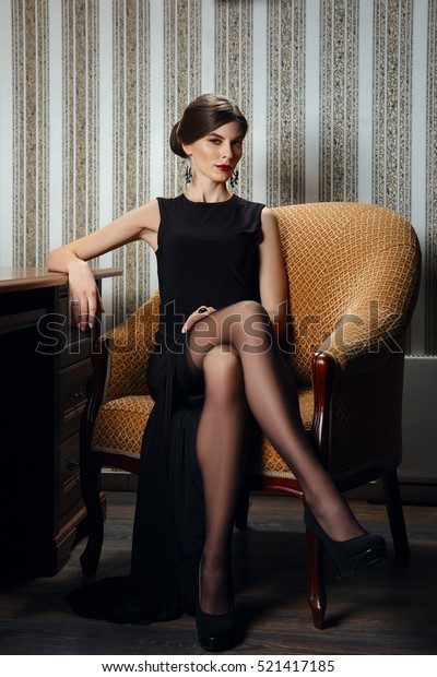 7b1a15473d07 Gorgeous lady in elegant evening black dress with deep cut in stockings.  Girl posing near