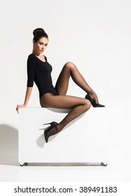 Gorgeous lady with hot legs sitting in sexy pose on a cube over isolated background.