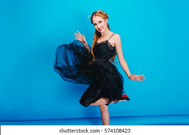 Gorgeous lady in nice black dress, fluttering fluffy skirt, dancing on a party. She has long blonde hair, wearing elegant shoes with high heels and cat ear headband with diamonds. Blue background.