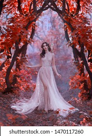 gorgeous lady perfect skin dark hair dressed in long gold lightly chic summer shiny transparent dress forest magic sorceress walks. trees with red leaves. Greek Goddess with white owl. Art photography
