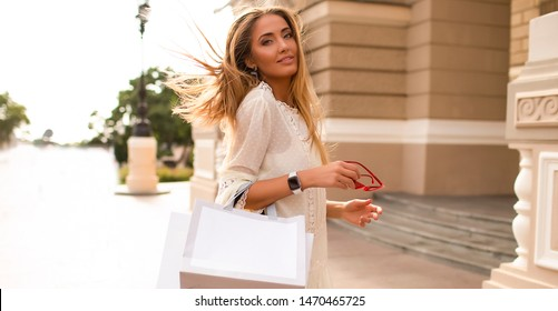 Gorgeous lady shopping and relaxing alone. Bags hanging on her hand, watch and accessories. Long hair waving on the wind. Stylish makeup, white teeth, blue eyes. Fashionable white dress.