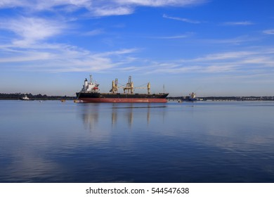 Gorgeous landscape of port of Huelva with cargo ships, pilot tugboat and cranes, with reflections in a sea in calm