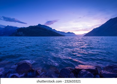 Gorgeous light and color after sunset. Panorama mountain range and sky with clouds reflected in surface of lake.