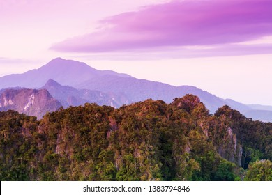 Gorgeous limestone mountains and beautiful clouds on summer dusk, purple light shines on limestone mountains and clouds backgrounds. Khao Phanom Bencha National Park, Krabi, Thailand.
