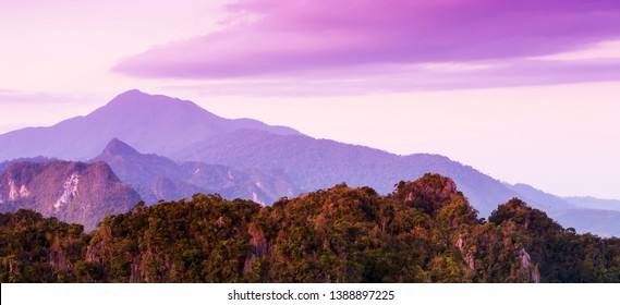 Gorgeous limestone mountains and beautiful clouds on summer dusk, purple light shines on limestone mountains and clouds backgrounds. Khao Phanom Bencha, Krabi, Thailand.