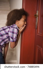 A gorgeous little 7yr old African girl peeping through a keyhole and looking shocked.