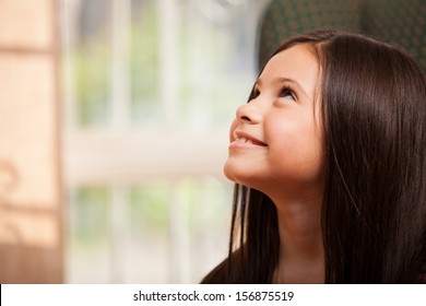 Gorgeous little girl smiling and looking up towards copy space