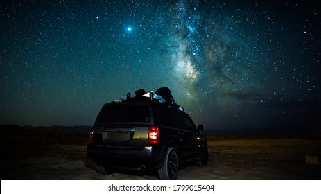 Gorgeous long exposure star-scape image with the beautiful milky-way in the background and a car in the desert for stargazing.