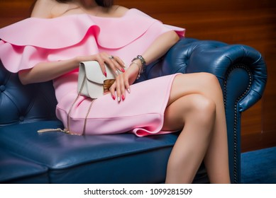 gorgeous long haired brunette woman posing on a blue leather sofa wearing a mini pink dress and holding a white purse, handbag. no face, unrecognizable person. luxury young adult girl
