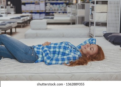 Gorgeous long haired woman lying on a new orthopedic bed at furniture store, copy space. Attractive female cusotmer trying comfortable mattress on sale at furnishings shop