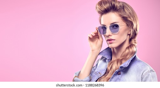 Gorgeous long-haired Blonde woman in Stylish denim jacket and fashion shorts. Lovable Lady in Trendy Outfit, blue Sunglasses. Sensual Model Girl in Studio on Pink Vanilla