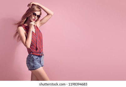 Gorgeous long-haired Blonde woman in Stylish striped blouse and fashion denim shorts. Glamorous Lady in Trendy Outfit, Sunglasses. Sensual Female model in Studio on Pink