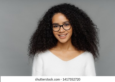 Gorgeous lovely curly woman with Afro hairstyle, feels glad, smiles gently at camera, wears optical glasses and white sweater, isolated on grey background. Happy emotions and feelings concept