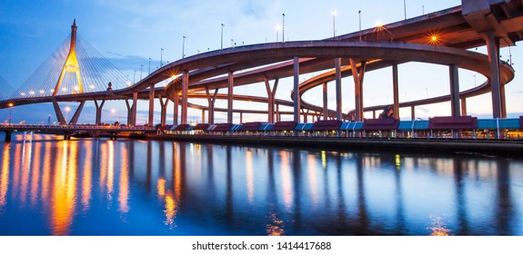 Gorgeous low angle view of highway interchange and suspension bridges at dusk, glowing lights reflection on surface of Chao Phraya River. Bhumibol Bridge, Thailand. Long exposure.