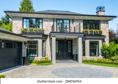Gorgeous luxury house with a balcony and beautiful landscaping on a sunny day. Home exterior.