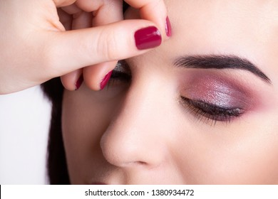 Gorgeous makeup in shades of pink covering the eyes of a beautiful woman.