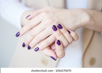 Gorgeous manicure, dark purple tender color nail polish, closeup photo. Female hands over simple background of casual clothes