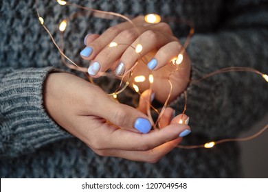 Gorgeous manicure, pastel tender color nail polish, closeup photo. Female hands hold a christmas light garland over grey knit background
