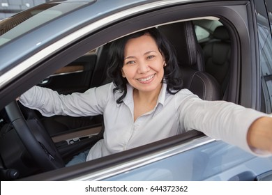 Gorgeous mature Asian woman smiling sitting in her new car making a selfie happiness positivity technology modern emotions expressive lifestyle travelling driving automobile concept