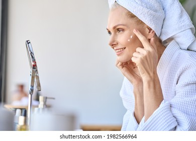 Gorgeous mid age older adult 50 years old blonde woman wears bathrobe in bathroom applying nourishing antiage face skin care cream treatment, looking at mirror doing daily morning beauty routine. - Shutterstock ID 1982566964