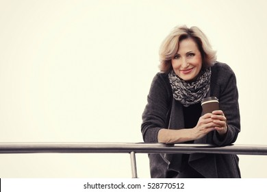 Gorgeous middle aged businesswoman with cup of coffee posing on urban background