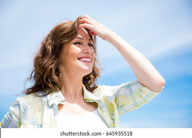 Gorgeous middle aged woman with a perfect smile against a blue sky