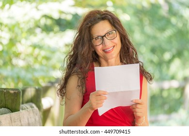 gorgeous middle-aged woman in a red dress and long brown wavy hair is reading a paper and smiling while wearing a pair of nerdy eyeglasses in a garden