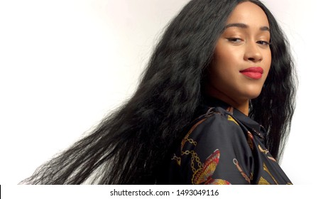 gorgeous mixed race model in studido shoot with long wavy wig on hair blowing