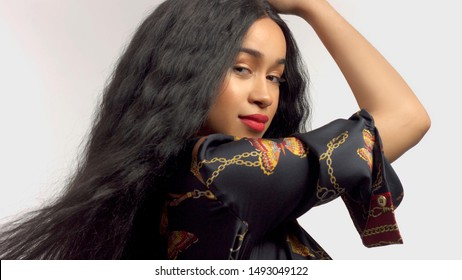 gorgeous mixed race model in studido shoot with long wavy wig on touches her hair