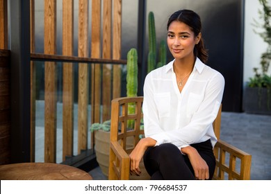Gorgeous mixed race woman sitting relaxed with peace of mind on home and garden patio