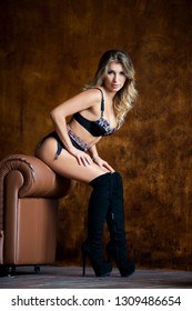 Gorgeous model woman blonde advertises fancy lingerie and knee high boots in studio. Perfect figure, well-groomed skin