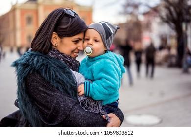Gorgeous mom cuddling happy baby boy outdoors