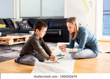 Gorgeous mother and her son playing at home,sitting on the floor in the living room,painting long coloring book for children,free time with kids for weekend concept