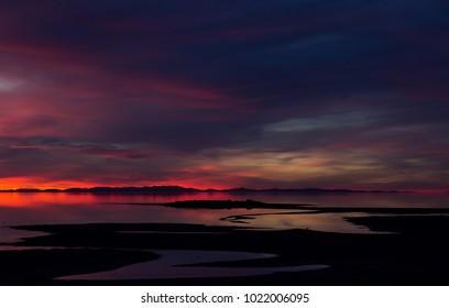 Gorgeous mountain sunset at Great Salt Lake taken from Antelope Island, Utah.  Mud trail cuts through the  salt flats taken at a wide angle