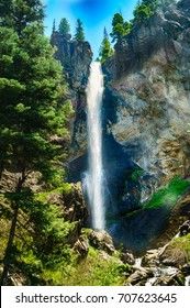 A gorgeous mountain waterfall cascading over the side of a cliff.