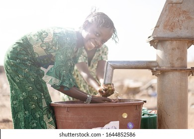 Gorgeous Native Malian African girl so happy to finally get healthy fresh water from an NGO tap in a village in Bamako, Mali