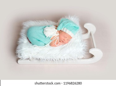 Gorgeous newborn baby boy in blue costume with bonnet with white tassel sleeping on small wooden sleigh as a crib. Christmas mood.
